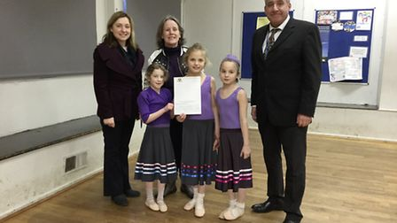 Three female ballet dancers from Heathlands School for the Deaf receiving a cheque