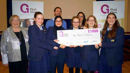 The winning team in the First Give competition, presenting a cheque to The Hospice of St Francis