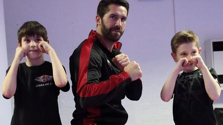 Jamie Stanway and Oliver Keenan, both 10, with martial arts action star Scott Adkins. Picture: Glen
