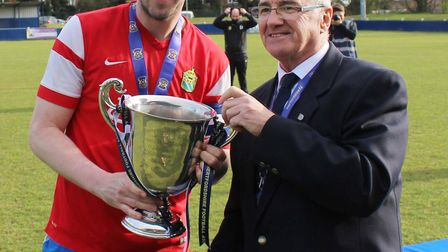 Skew captain Andy Saul receives the cup from Herts FA's John Burlison.