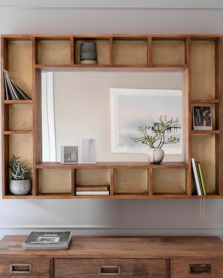 This pigeonhole mirror includes a mango wood surround with a delicate brass inlay. The boxes can hou