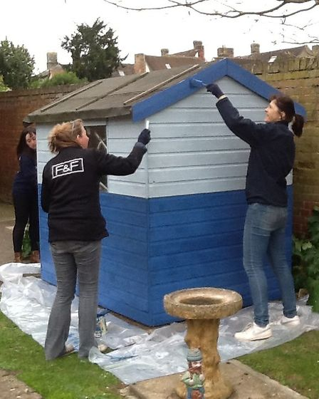 The tesco team get stuck in painting the shed.