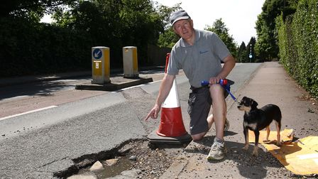 John Armstrong next to the large pothole on Sandpit Lane which caused damage his son's car. Picture: