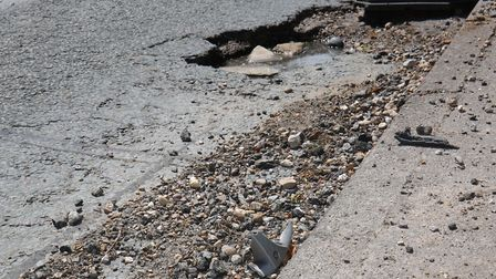 Evidence of damage to car wheels and the road surface lie next to the large pothole on Sandpit Lane.