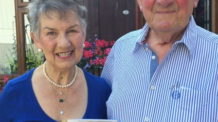 Mavis and George Howard with their card from the Queen.