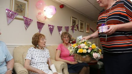 Ora Tydeman is presented with some flowers by care home manager Angela Johnson as she celebrates her