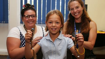 Teacher Miss Pena and headteacher Mrs Schofield with Edie, 8, holding her plaits ready to give to th