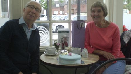 Peter and Ann Cook celebrating their diamond wedding anniversary with cake at Tasty Bites cafe.