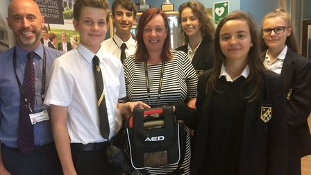 A group of Year 9 students with David Atkins, left, and Karen Bickers holding one of the two new def