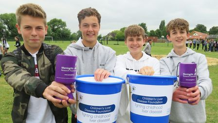 Students holding charity collection buckets at Bassingbourn Village College fete.