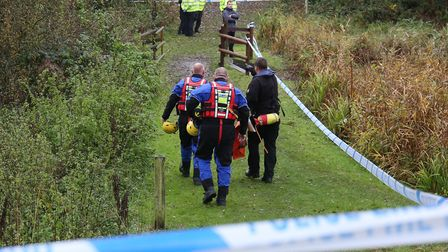 Police in safety gear prepare to remove the body from Southdown Pond. Photo: DANNY LOO