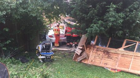 Driver has a lucky escape after smashing through a fence and a shed