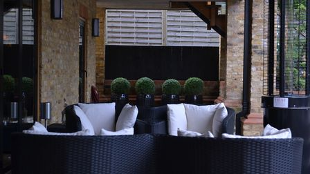 Kate Gould used striking black exterior furniture accented with soft cream cushions to complete the