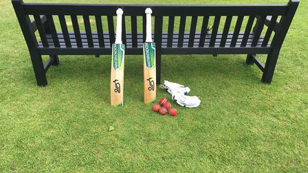 Cricket bats are propped up against a bench before play