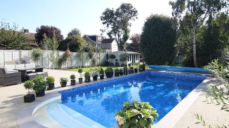The pool is surrounded by a large resin patio area