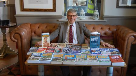 Roger Protz with the many editions of the Good Beer Guide he has edited over the years.