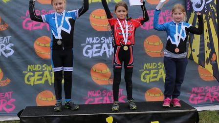 Ruby O'Dell (centre) on the top step of the podium following her victory.