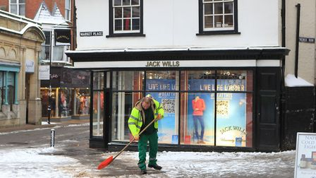 A worker shovels snow to clear the pavements of Market Place. Photo: DANNY LOO