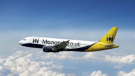 A Monarch aircraft flying through the clouds.