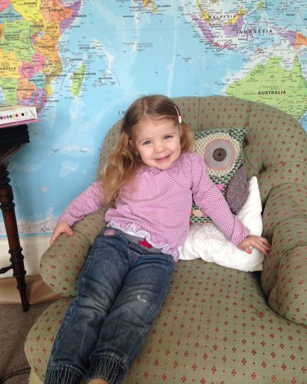 Richard Burr's daughter Genevieve, sitting in front of their map feature wall [PA Photo/Handout]