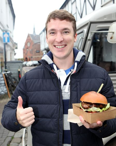 A young man is pleased with his purchase of a flame grilled burger.Picture: Craig Shepheard