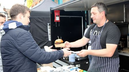 A young man buys a flame grilled burger.Picture: Craig Shepheard