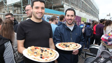 Two men hold fresh cooked pizzas.Picture: Craig Shepheard