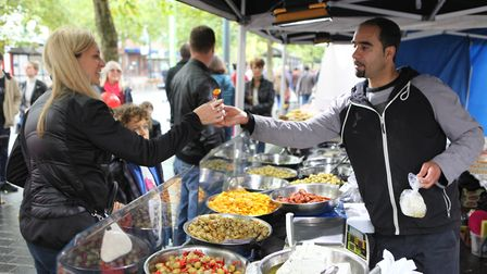 A stall holder hands over a sample of his olives to a lady.Picture: Craig Shepheard