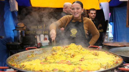 A cook stirs a large paella.Picture: Craig Shepheard