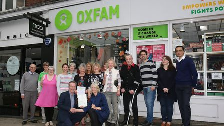 Oxfam trading director Andrew Horton (front left) presents store manager Chris Rhodes (front right)