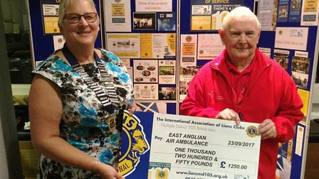 Peter Plant receiving the cheque for East Anglian Air Ambulance from Lion president Pam Wallwork.