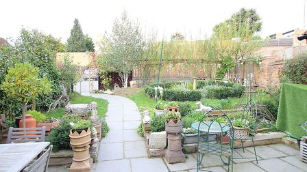 The private landscaped garden features mature planting and shrubs