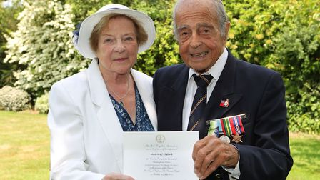 Pam and John Clifford with their invitation to Buckingham Palace to meet The Princess Royal with oth