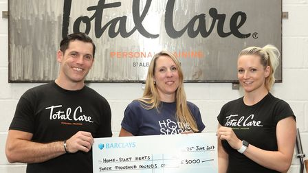 Suzy from Home-Start being presented with a cheque from Total Care Personal Training by Tommy and Li