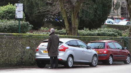 A man struggles to make sense of the parking signs on Romeland Hill