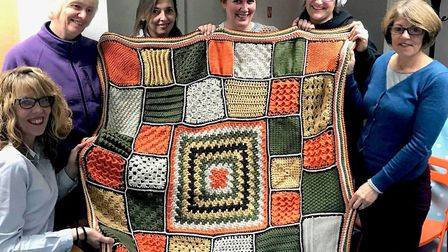 Laura Whitford, centre, with her fellow yarn crafters and the blanket they made for Children in Need