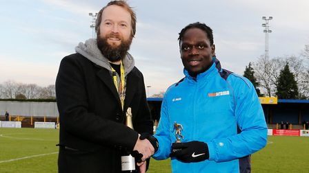 St Albans City's Solomon Sambou receives his player of the month award for November from James Frase
