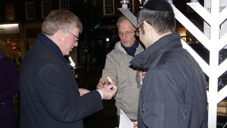 Deputy Mayor of St Albans Cllr Jamie Day (L) lights a candle with the help of synagogue member Steve