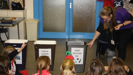 Waste awareness officer Lizzie Shepherd showing a group of Rainbows how to sort materials for recycl