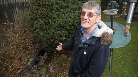Disabled Willem Hofland in front of his pond which St Albans council have deemed a health and safety