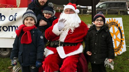 Father Christmas meets Marc, holding Evan, with Tyler, left, and Noah, right. Picture: ARCHANT