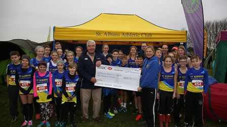 Chair of 948 sports foundation Bryan Short presents a cheque to St Albans Striders volunteer Deborah