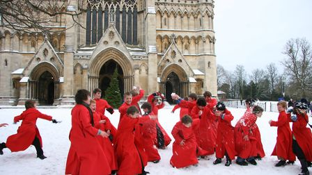 Choristers throwing snowballs outside St Albans Cathedral
