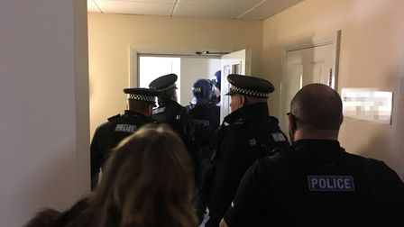Entering the building as part of Operation Retuned. Picture: Archant