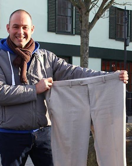 Tom Smith, 44, with a pair of trousers he used to wear before he lost more than four stone. Picture: