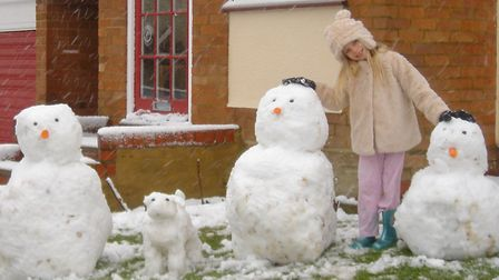 Poppy with her snow family, which she got up early yesterday morning to make. Picture: Ray Dowding