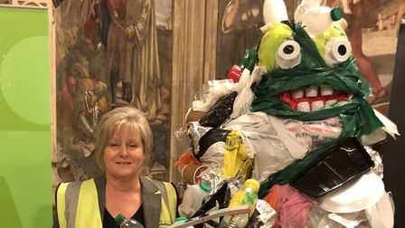 Anne Main in a high visibility jacket next to a pile of plastic waste.