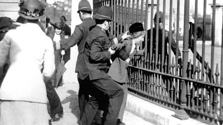 A policeman restrains a demonstrator as suffragettes gathered outside Buckingham Palace, where an at