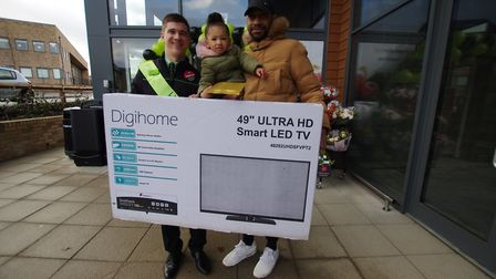 Store manager Joel Mattless with TV winner Niccolas Charles and daughter Violet