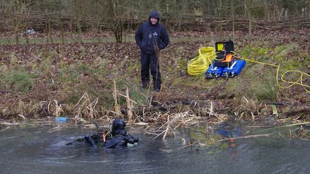 Police divers in action at a pond near Hinchingbrooke Park